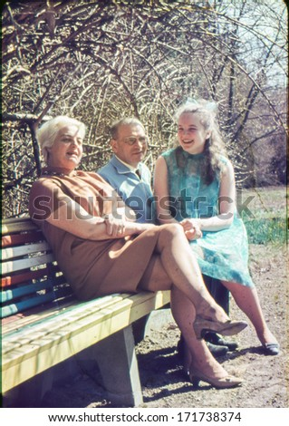 Vintage photo (scanned reversal film) of mature parents with a teenager daughter in garden, sixties