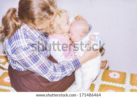Vintage photo (scanned reversal film) of mother with little children, 1982 - stock photo