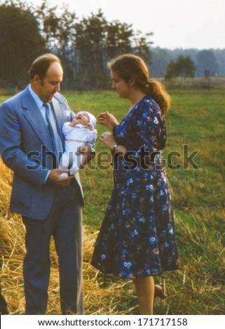 Vintage photo (scanned reversal film) of young parents with a baby boy (August 1982) - stock photo