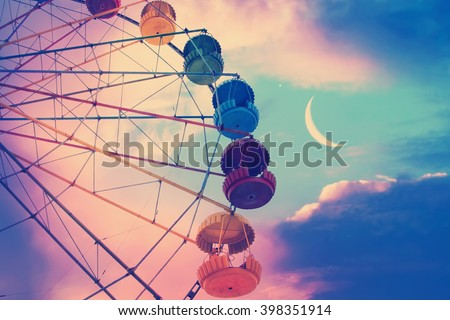 Vintage photo with ferris wheel against the moon colorful sky  - stock photo