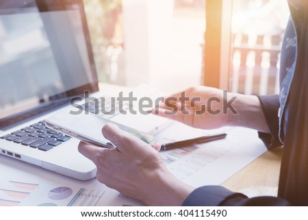 Vintage photo woman's hands holding a credit card and using smart phone, online shopping,  - stock photo