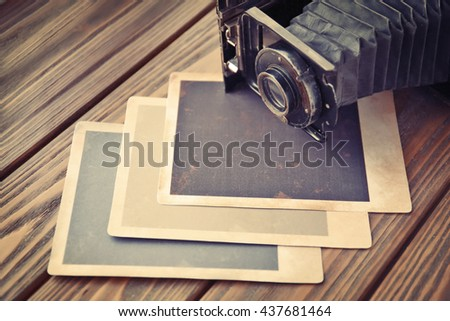 Vintage photos with camera on wooden background - stock photo