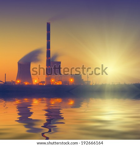 Vintage picture. Coal power plant with rising sun, reflected in water.  - stock photo