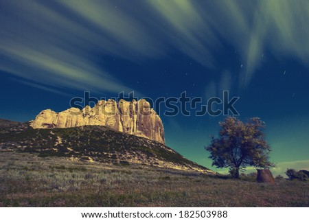 Vintage picture. High cliff in a moon light with a beautiful moving clouds and lonely tree - stock photo