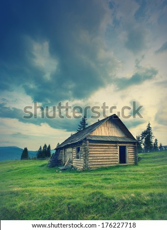 Vintage picture. Mountain landscape with a great sky and a wooden house