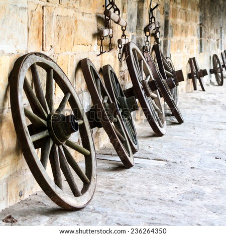Vintage Picture of old wooden wheels on a castle in Bavaria, Germany in Europe . Still Life Picture. Stone walls. - stock photo