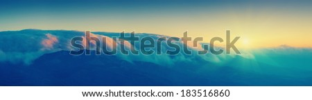Vintage picture. Sunrise in the mountains with beautiful textural clouds cover the top of the mountains - stock photo