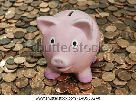 Vintage piggy bank sitting on large penny pile. - stock photo