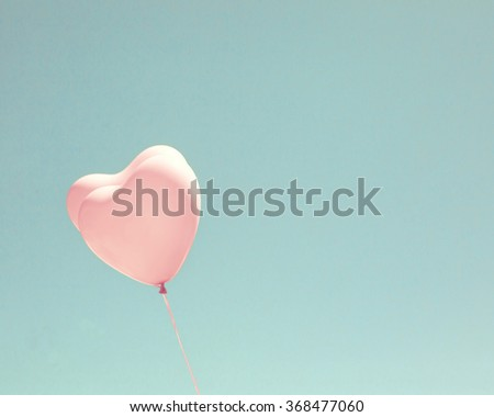 Vintage Pink balloons flying in a blue sky