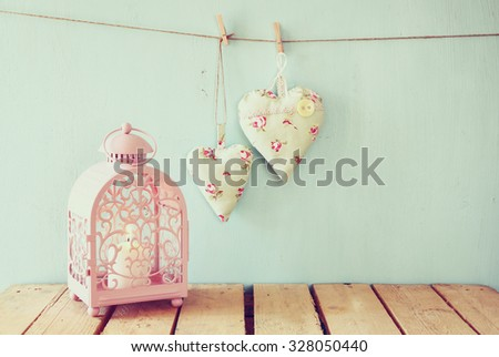 vintage pink classical frame, fabric hearts hanging on the rope and lantern with garland lights, on wooden table. retro filtered image  - stock photo