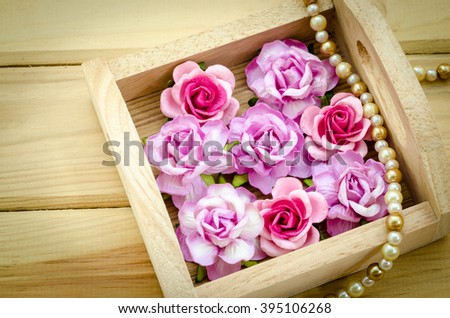 Vintage pink rose and Pearl Necklace on wooden background. Love concept. - stock photo