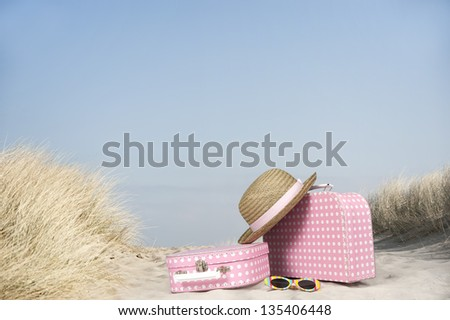 vintage pink with white dots suitcase and straw summer hat at the beach - stock photo