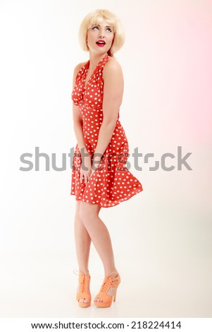 Vintage pinup style. Full length of beautiful stylized young woman. Attractive girl in blond wig and retro spotted red dress on pink. Disguise. Studio shot.