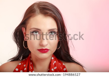 Vintage pinup style. Portrait of beautiful stylized young woman. Attractive brunette girl in retro spotted red dress on pink. Disguise. Studio shot.