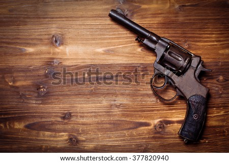 Vintage pistols on wooden background - stock photo