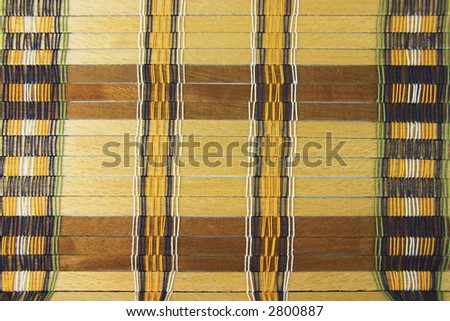 Vintage placemat with natural, unpainted wooden planks and colorful threads - background, texture - stock photo