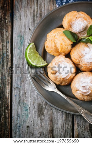 Vintage plate of homemade cakes profiteroles on old wooden table. Top view. - stock photo