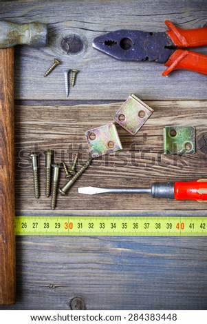 Vintage pliers, screwdriver, screws, hammer, angles and roulette. Still life with old tools - stock photo