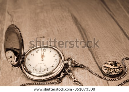 Vintage pocket clock showing five to twelve. Happy New Year! - stock photo