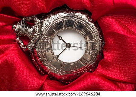 Vintage Pocket Mechanical Watch On Red Satin Background - stock photo