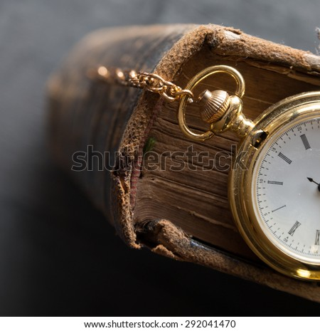 Vintage pocket watch and old book, symbols of time