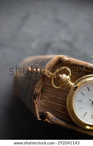 Vintage pocket watch and old book, symbols of time with copy space