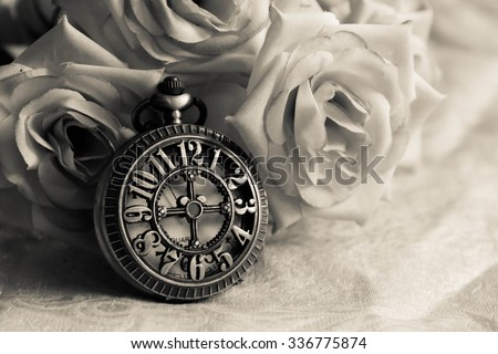 Vintage pocket watch  and roses on fabric time concept,Black and white - stock photo