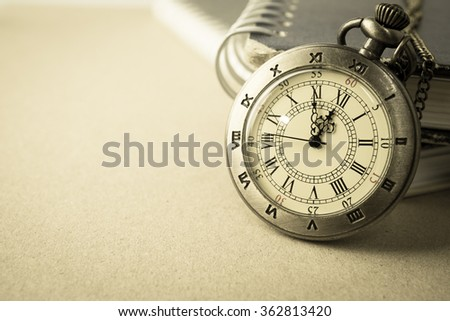 vintage pocket watch and the book on craft paper - stock photo