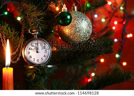 Vintage pocket watch hanging on Christmas tree near lighting candle