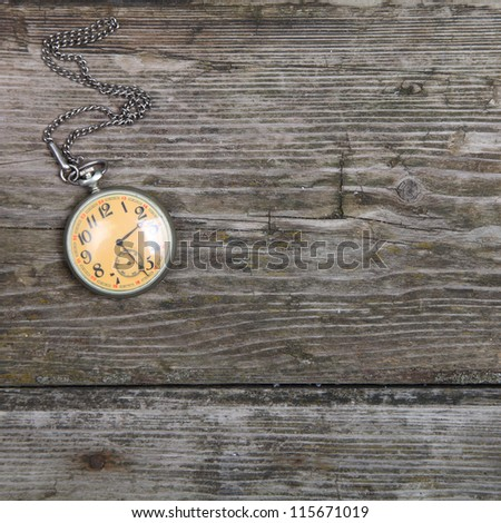 Vintage pocket watch on chain on wooden background