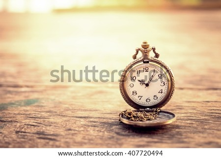 vintage pocket watch on grunge wood log - stock photo