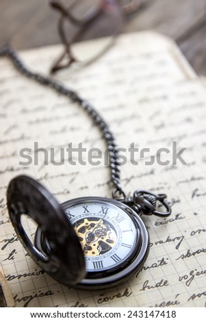 Vintage pocket watch on old book closeup - stock photo