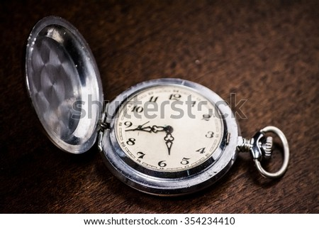 Vintage pocket watch on wooden desk. Symbol of time, deadlines, and rush. Conceptual background image. - stock photo