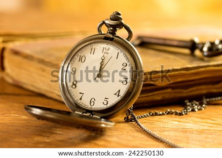 Vintage pocket watch on wooden surface against old book - stock photo