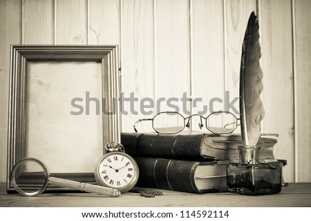 Vintage pocket watch, photo frame, quill and inkwell, books magnifying glass, specs on a table in front of wooden background - stock photo