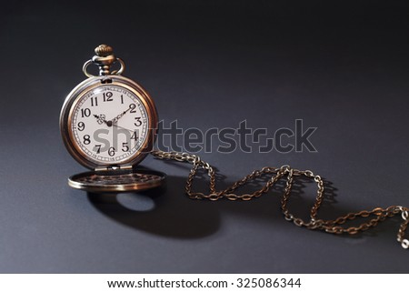 Vintage pocket watch with chain on dark background
