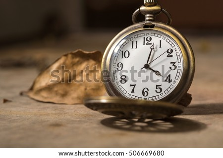 vintage pocket watch with Dry leaf background for time concept