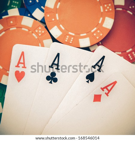 vintage poker, four aces over a background with casino chips - stock photo