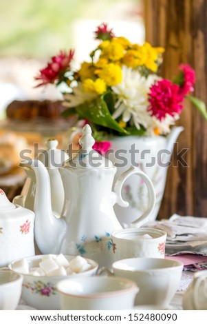 Vintage porcelain tea and coffee cups and flower decoration - stock photo