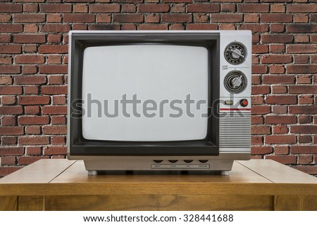 Vintage portable television and old wood table with red brick wall. - stock photo