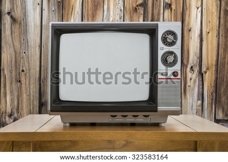 Vintage portable television and table with rustic cabin wall. - stock photo