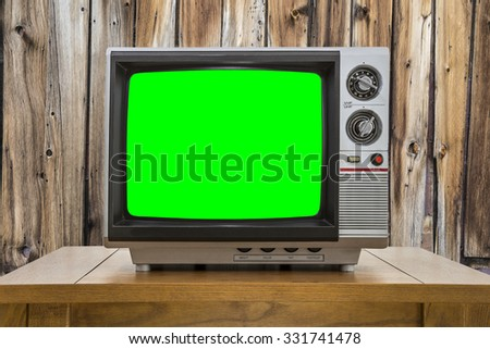 Vintage portable television with chroma key green screen and rustic cabin wall. - stock photo