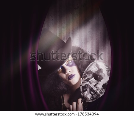 Vintage portrait of a beautiful theater stage performer play acting a masquerade show with carnival mask behind velvet curtains. Masked drama - stock photo