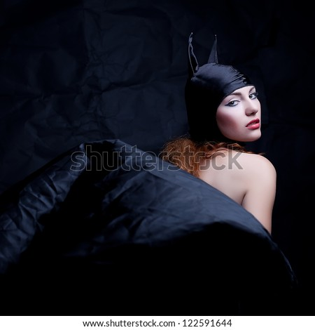 vintage portrait of a glamorous animal red-haired girl over wrinkled black paper background. studio shot - stock photo