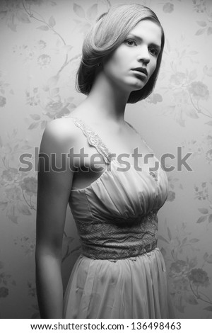 Vintage portrait of a glamorous doll-like retro girl posing in gorgeous classic dress . Hollywood style (film noir). Black and white (monochrome) studio shot
