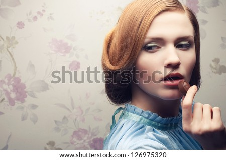 Vintage portrait of a glamorous red-haired (ginger) girl in blue dress eating chocolate candy. Close up. Copy-space. Studio shot - stock photo