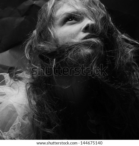Vintage portrait of a gorgeous queen-like girl posing over wrinkled black paper background. Retro (classic) style. Close up. Studio shot - stock photo