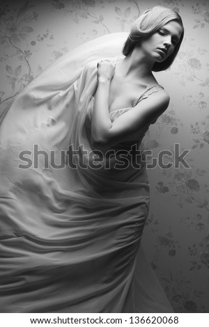 Vintage portrait of a happy glamorous blonde girl posing in great flying white dress and dancing. Retro (classic) style. Black and white (monochrome) studio shot - stock photo
