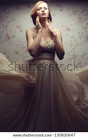Vintage portrait of a happy glamorous red-haired (ginger) girl posing in great flying beige dress and dancing. Studio shot