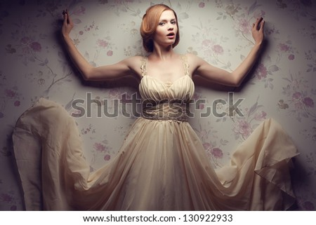 Vintage portrait of a happy glamorous red-haired (ginger) girl posing in great flying beige dress, dancing with hands up and singing. Retro style. Studio shot